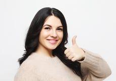 Kvinnlig g?rande tumme f?r lycklig ung caucasian upp tecken och att le glatt och att visa hennes service och att respektera till  royaltyfri fotografi