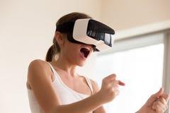 Kvinnlig gamer som bär VR-exponeringsglas som spelar virtuell verklighetmobilG Arkivbild