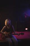 Kvinnlig gitarrist som spelar gitarren, medan sitta på etapp royaltyfria bilder