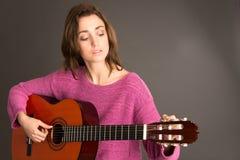 Kvinnlig gitarrist som trimmar gitarren arkivbild