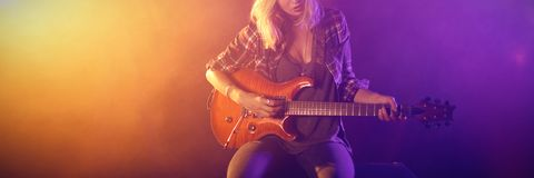 Kvinnlig gitarrist som utför i nattklubb royaltyfria bilder