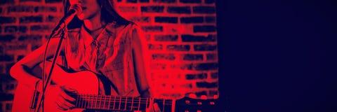 Kvinnlig gitarrist som utför på klubban arkivfoto