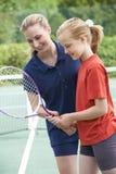 Kvinnlig Giving Lesson To för tennislagledare flicka royaltyfri bild