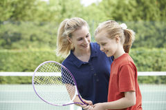Kvinnlig Giving Lesson To för tennislagledare flicka arkivbild