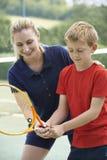 Kvinnlig Giving Lesson To för tennislagledare pojke royaltyfri foto
