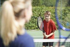Kvinnlig Giving Lesson To för tennislagledare pojke arkivfoton