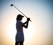 Kvinnlig golfare på solnedgången Arkivfoto