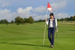 Kvinnlig golfare som rymmer flaggan från hålet Royaltyfri Fotografi