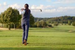 Kvinnlig golfare som slår golfbollen Arkivbild
