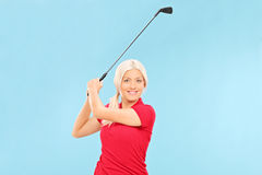 Kvinnlig golfare som svänger en golfklubb Arkivfoto