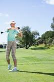 Kvinnlig golfare som tar ett skott Arkivbilder