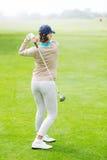 Kvinnlig golfare som tar ett skott Royaltyfri Foto
