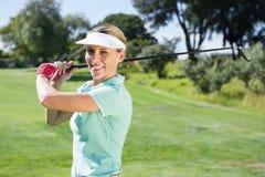 Kvinnlig golfare som tar ett skott och ler på kameran Arkivfoto