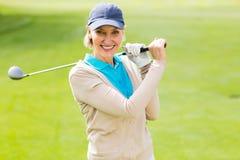 Kvinnlig golfare som tar ett skott och ler på kameran Royaltyfri Bild