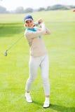 Kvinnlig golfare som tar ett skott och ler på kameran Royaltyfria Foton