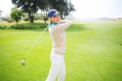 Kvinnlig golfare som tar ett skott och ler på kameran Royaltyfri Foto