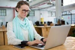 Kvinnlig grafisk formgivare som använder bärbara datorn på skrivbordet fotografering för bildbyråer