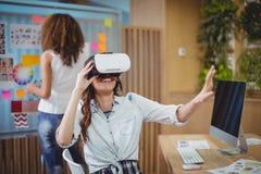Kvinnlig grafisk formgivare som använder virtuell verklighethörlurar med mikrofon med hennes kollega i bakgrund royaltyfri bild
