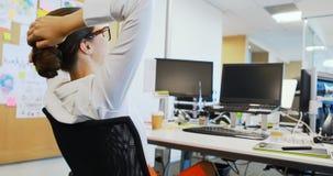 Kvinnlig grafisk formgivare som kopplar av på skrivbordet stock video