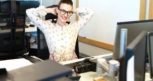 Kvinnlig grafisk formgivare som kopplar av på skrivbordet lager videofilmer