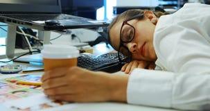 Kvinnlig grafisk formgivare som sover på skrivbordet stock video