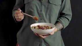 Kvinnlig hällande honung på granola med torkad bär och choklad stock video