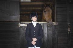 Kvinnlig hästrygg Rider With Horse In Stable Arkivbild