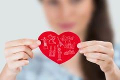 Kvinnlig hållande hjärta med henne armar och berömda touristic symboler Arkivfoto