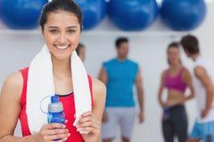 Kvinnlig hållande vattenflaska med konditiongrupp i bakgrund Arkivbilder