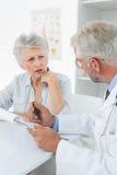 Kvinnlig hög patient som besöker en doktor Royaltyfri Bild
