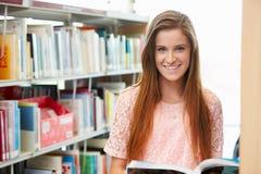 Kvinnlig högskolestudent Studying In Library royaltyfri fotografi