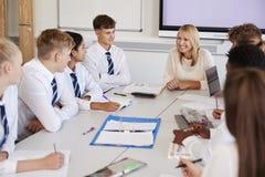 Kvinnlig högstadiumlärare Sitting At Table med tonårs- elever som bär enhetlig undervisande kurs fotografering för bildbyråer