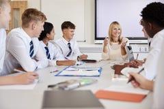 Kvinnlig högstadiumlärare Sitting At Table med tonårs- elever som bär enhetlig undervisande kurs arkivbild
