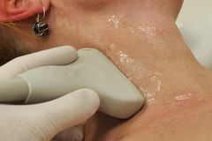 Kvinnlig hals för linjär ultraljudsondscanning i longitudal position Arkivfoton