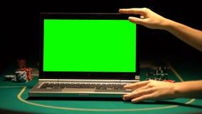 Kvinnlig handöppningsbärbar dator, pokerchiper omkring, online-kasino som annonserar lager videofilmer