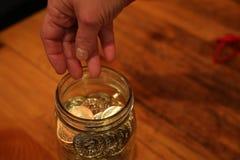 Kvinnlig hand över kruset mycket av mynt Royaltyfri Bild