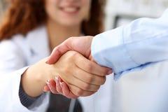 Kvinnlig hand för medicindoktorsskaka som hälsningar med affärskvinnan royaltyfria bilder