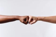 Kvinnlig hand för svart afrikansk amerikanlopp som trycker på knogar med den vita Caucasian kvinnan i blandras- mångfald Royaltyfria Bilder