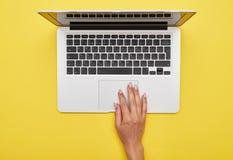 Kvinnlig hand genom att använda touchpaden av bärbara datorn arkivfoto