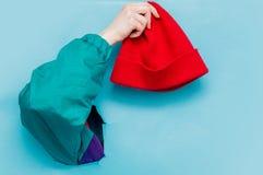 Kvinnlig hand i 90-talstilomslaget som rymmer den röda hatten royaltyfri bild