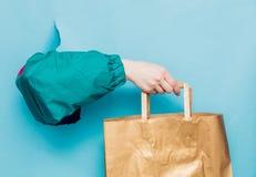 Kvinnlig hand i 90-talstilomslaget som rymmer shoppingpåsen arkivbild