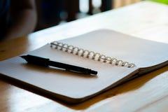 kvinnlig hand med blyertspennahandstil p? anteckningsboken p? coffee shop kvinna som arbetar vid handhandstil p? brevpapper p? tr arkivbilder