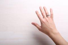 Kvinnlig hand med cirkeln på fingret Arkivbild
