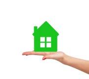 Kvinnlig hand med den lilla modellen av huset som isoleras på vit Royaltyfri Foto