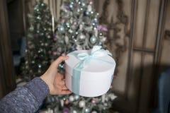 Kvinnlig hand med en gåva nytt år Ferien till oss kommer arkivfoto