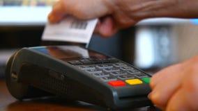 Kvinnlig hand med en kontokort genom att använda terminalen för betalning Begreppet av icke-kassa betalning lager videofilmer