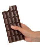 Kvinnlig hand med en tegelplatta av svart choklad royaltyfri bild