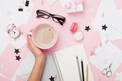 Kvinnlig hand med kaffekoppen, macaron, kontorstillförsel, gåvan och anteckningsboken på pastellfärgad skrivbords- sikt Rosa kvin royaltyfria foton