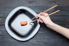 Kvinnlig hand med pinnar och sushi Svart träbakgrund Arkivbild