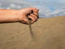 Kvinnlig hand med sand mot dyerna av Maspalomas med blå himmel och moln i bakgrunden arkivbilder